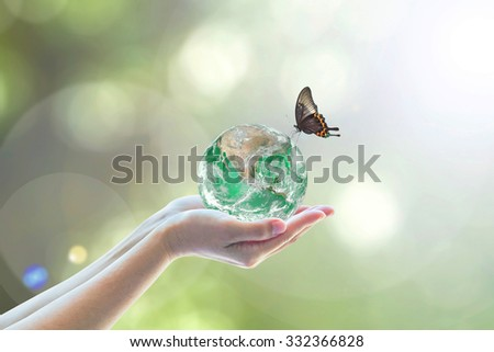 Green globe with butterfly on human woman hands on blurred nature background of greenery bokeh: Harmony ecosystems of natural world living lives concept idea: Elements of this image furnished by NASA - stock photo