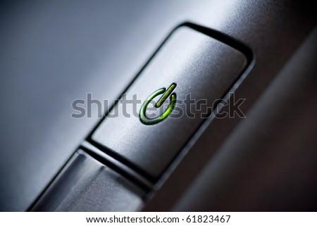 Green glowing power button. Closeup shot. - stock photo