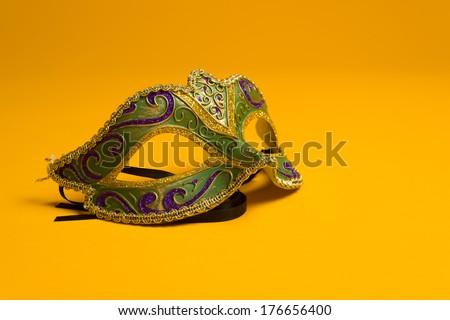 Green, gold, purple mardi gras mask on a bright yellow background - stock photo