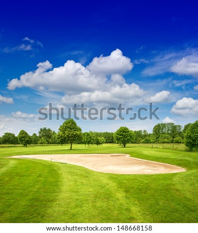 green golf course and dramatic blue sky. european field landscape - stock photo
