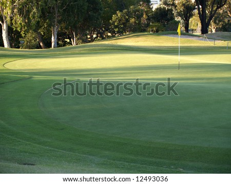 Green Golf Course Series - Putting green with flag and mown concentric patterns - stock photo