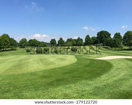 Green golf field landscape with blue sky