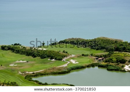 Green Golf Field Over Blue Sea - stock photo