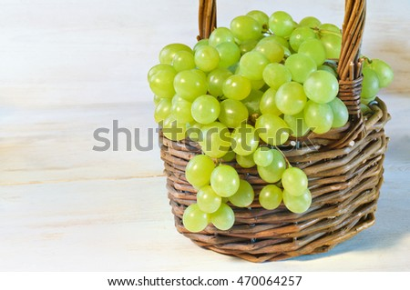 Green grape in basket on wooden table. Close-up