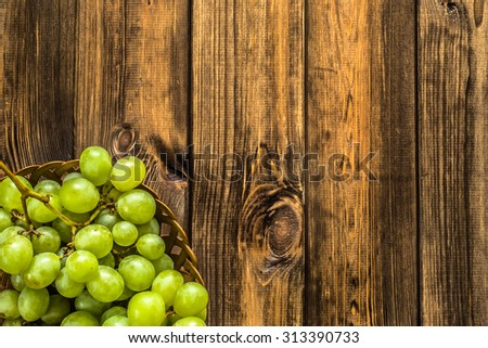 Green grapes fruits in the basket on rustic wood background.