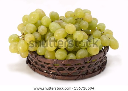 Green grapes in basket on a white background.