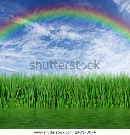 Green grass and a rainbow in the sky reflected in the water - stock photo