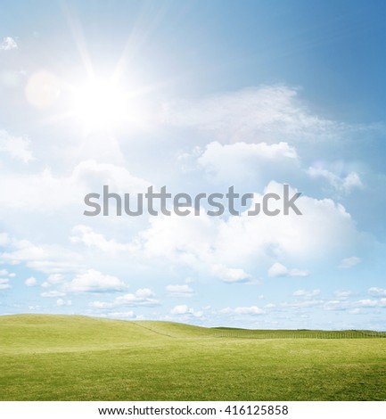 Green grass and sun in blue sky - stock photo