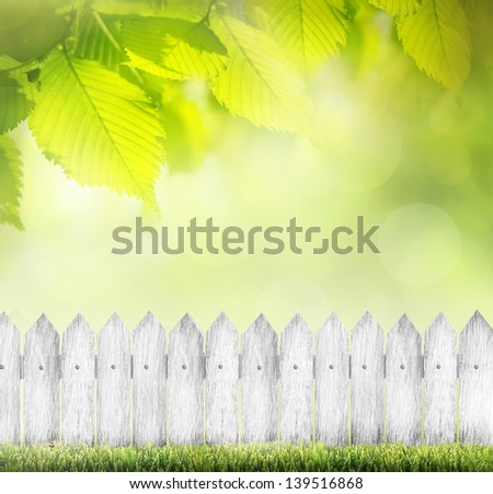 green grass and white wood fence over bokeh - stock photo