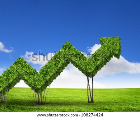 Green grass arrows against blue sky with white clouds - stock photo