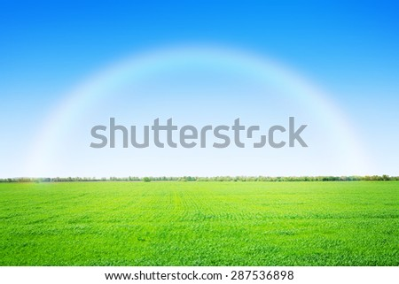Green grass field and clear blue sky with rainbow - stock photo
