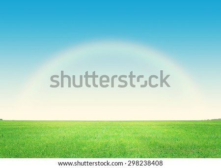 Green grass field and deep blue sky with rainbow background - stock photo
