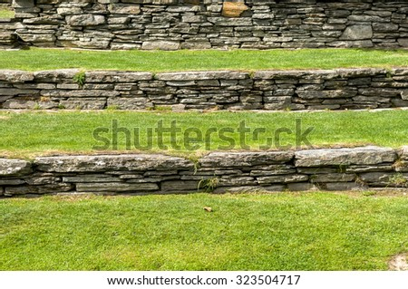 green grass field and stone wall