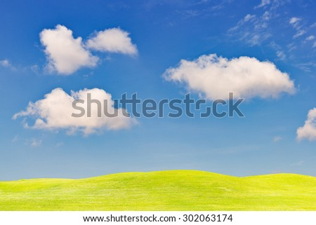Green grass field in clear blue sky and white cloud - stock photo