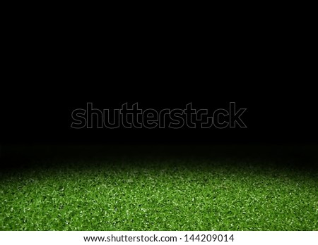 Green grass field with spotlight - stock photo