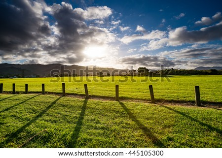 Green grass field, wooden Fence and mountain on horizon at summer morning. American spring sunrise in Denver Colorado USA - stock photo