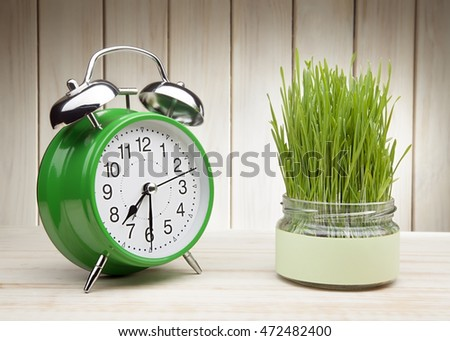 green grass grown in a pot and green alarm clock on white wooden table