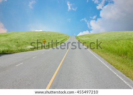 green grass hill with  blue sky cloud background and road way