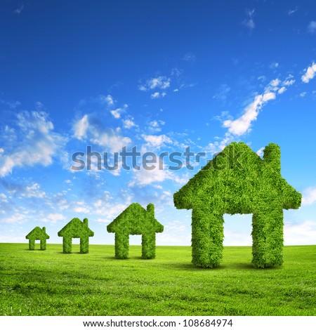Green grass  house symbol against blue sky - stock photo