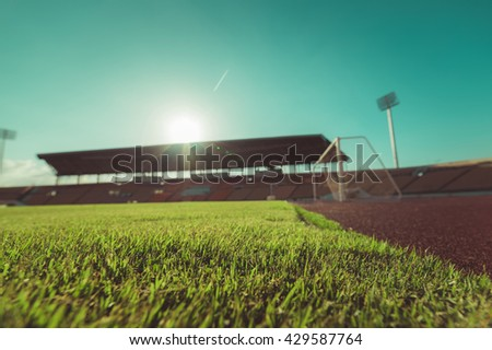 Green grass in soccer stadium. soccer field  vitage tone. soccer stadium on blue sky.  - stock photo