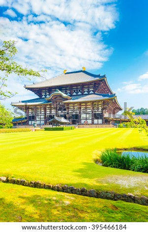 Green grass in the wide lawn in front of entrance facade on grounds of main Great Buddha Hall, Daibutsuden, on a beautiful, blue sky summer morning at Todai-ji temple in Nara, Japan. Vertical - stock photo