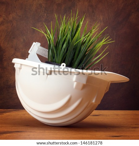 Green grass in white helmet- environmental friendly industry concept - stock photo
