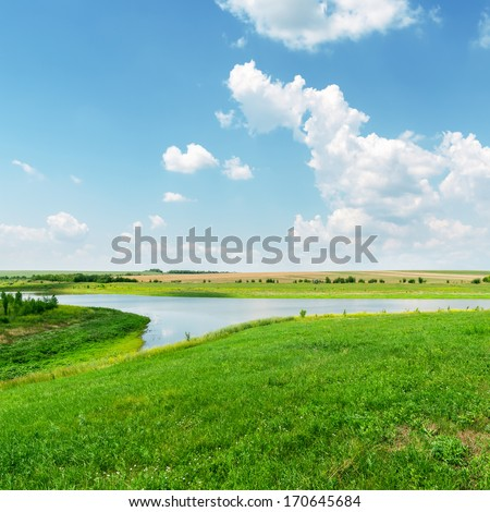 green grass, river and clouds in blue sky - stock photo