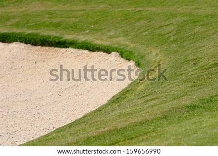 Green grass surrounding a golf bunker. - stock photo