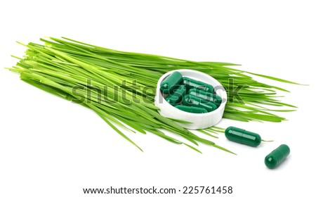 Green grass, tablets, pills and capsules isolated on white - stock photo