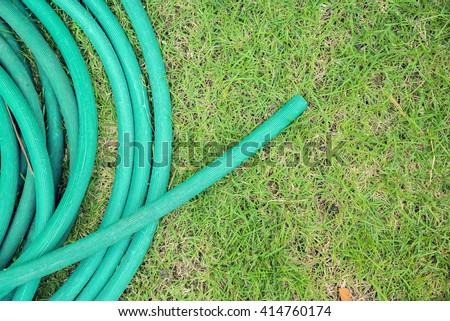 Green grass water hose - stock photo