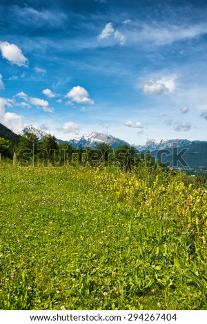 Green grassy plateau in the Berchtesgaden Alps in Bavaria, Germany overlooking alpine peaks with a smattering of snow - stock photo