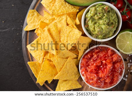 Green Guacamole with nachos and avocado on stone background - stock photo
