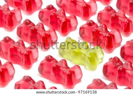 Green gummy bear among red - stock photo