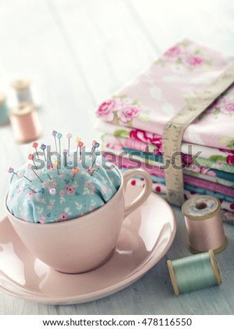 Green handmade floral pincushion in a pink cup with old spools of thread, sewing concept background