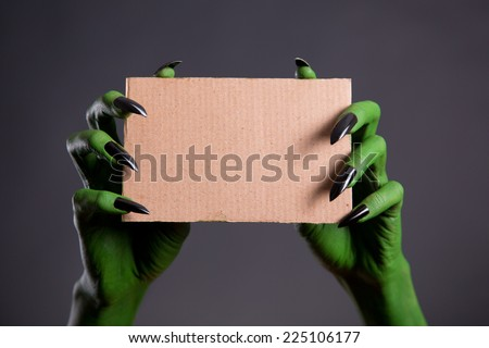 Green hands with black nails holding empty piece of cardboard, Halloween theme