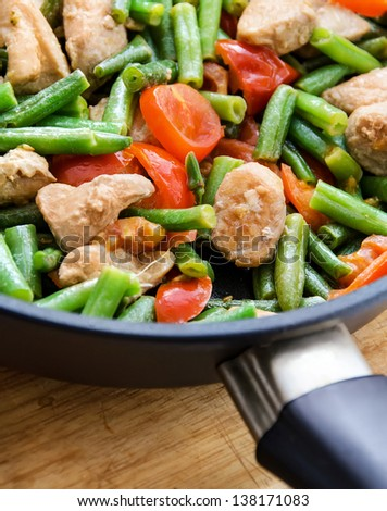green haricot with meat and tomatoes on a frying pan