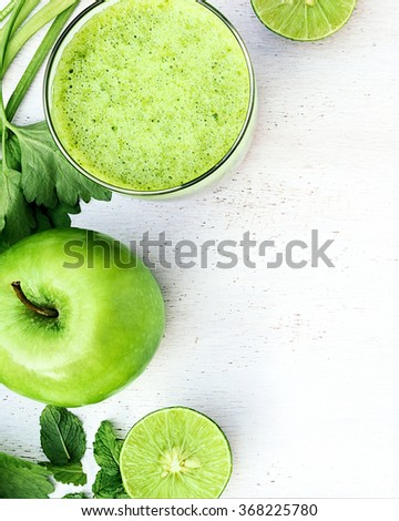 Green healthy drink. Vegetable juice, apple, sliced lime, leaves of mint and celery on the white wooden background. Vegetarian food. Detox - stock photo
