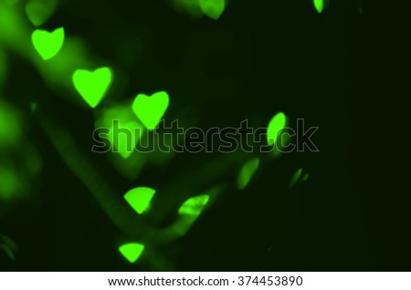 Green hearts texture. Hearts Bokeh in dark. Defocused lights background. Color Bokeh on a dark background with hearts for use in graphic design. Valentine's style lights. St. Valentine's Day. - stock photo