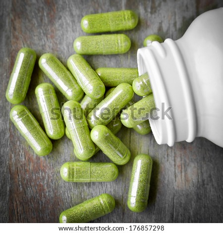 Green herb capsules spilling out of a bottle - stock photo