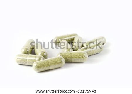 green herbal medicine capsule isolated on white background - stock photo