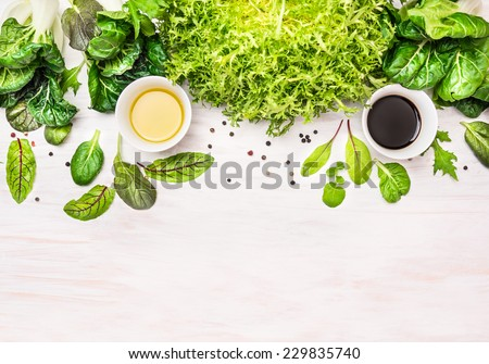 green herbs mix salad with dressing, preparation on white wooden table, food background with place for text - stock photo
