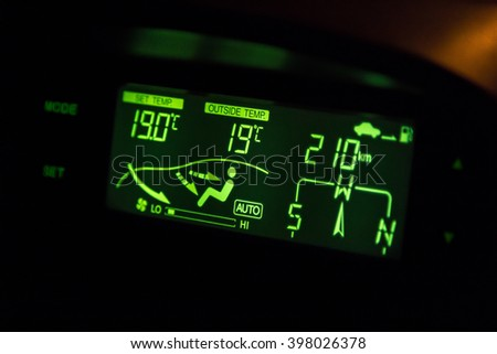 green highlighted car air conditioner control panel at night - stock photo