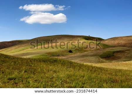 Green hill and cloud in sky - stock photo