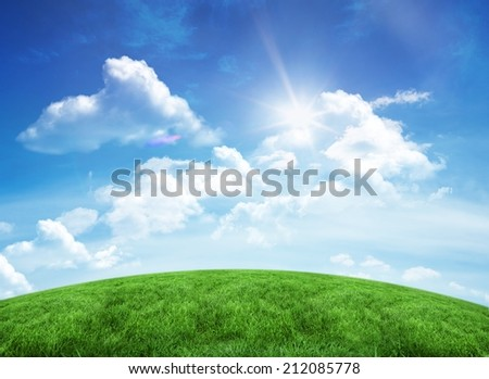 Green hill under blue sky with copy space - stock photo
