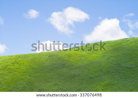 Green hill with blue sky with soft white clouds in the background - stock photo