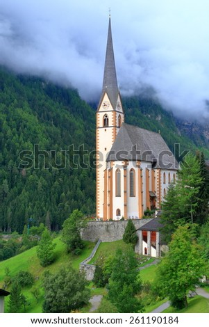 Green hills and dark clouds around tall building of St Vincent church, Heiligenblut, Austria