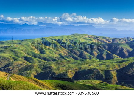green hills and sea landscape, location - Wellington, North Island, New Zealand - stock photo