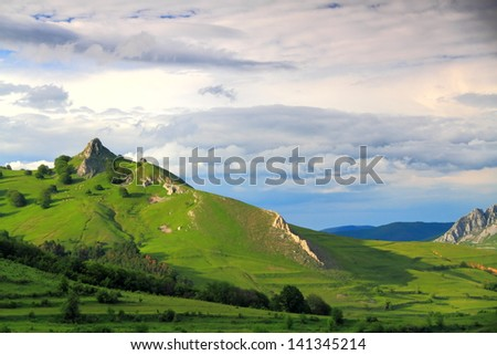 Green hills and valley at sunset - stock photo