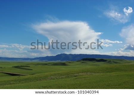 Green hills, mountains and particular clouds, Wyoming - stock photo