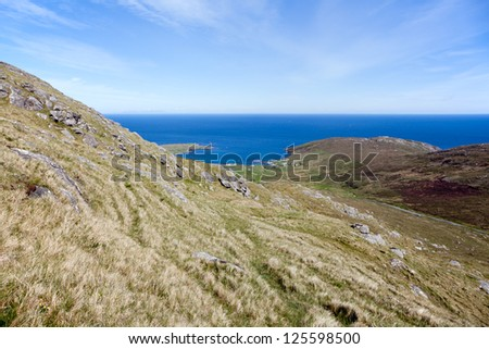Green hills overlooking the sea at Barra . Landscape of Outer Hebrides, Scotland . - stock photo
